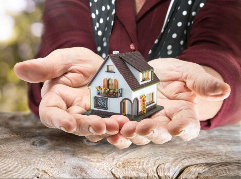 Woman Holding Toy House in Her Hands - Protect your house from Medicaid concept