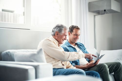 Man and Senior Father on Couch Discussing Estate Planning