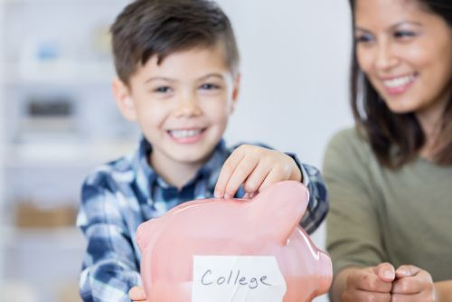 Boy Putting Coins in 529 Plan Piggybank