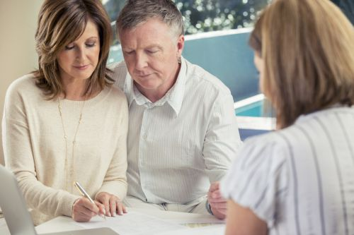 Couple Signing Paper to Choose Agent for Power of Attorney