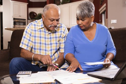 Indian man and African descent woman, senior adult couple work together to pay their monthly bills. They are calculating expenses versus budget income. Many invoices on living room table. Kitchen background. Frustration among middle-class people. Great imagery for election season: home finances, recession, past due bills, mortgage, debt, stress, worry, taxes.