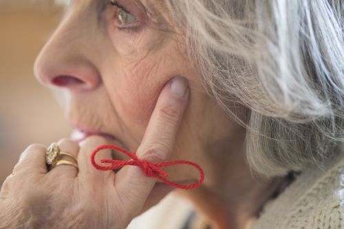 Senior Woman With Alzheimer's With String Tied Around Finger As Reminder