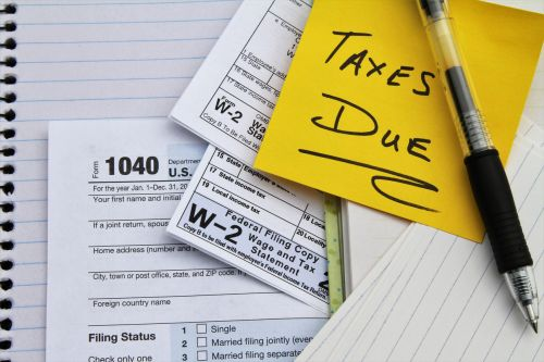 Tax return forms and wage statements with a note saying Taxes Due. An IRS tax return form 1040 and two W-2 Wage and Tax Statement forms indicating wages were earned from two employers.