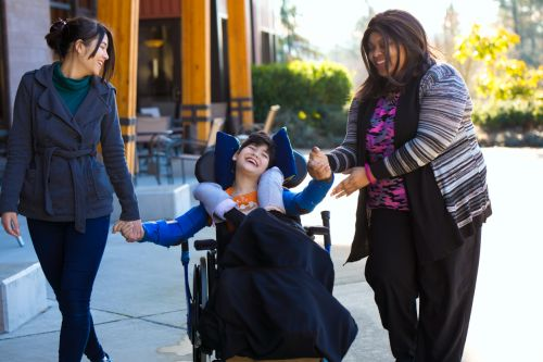 Disabled child in wheelchair holding hands with caregivers while on a walk outdoors