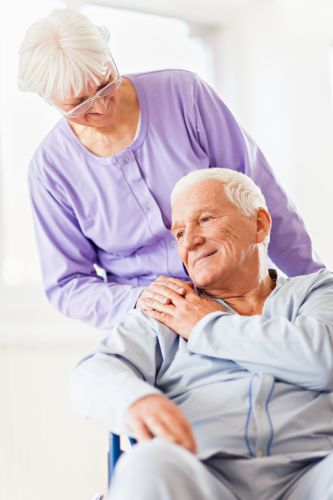 Close up of a senior patient holding hands with his wife in hospital