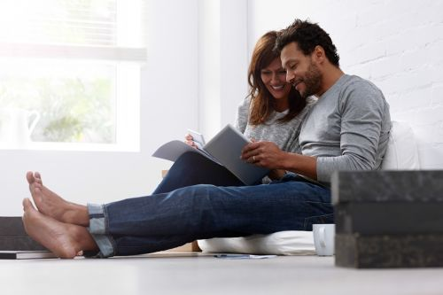 Couple sitting together with bills, calculator and digital tablet calculating their expenses