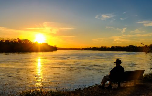 Senior man sitting on a bench watching sun go down on the river.