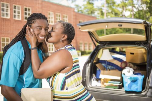Mother is helping her son unpack his car and says goodbye with a kiss as he moves into the college campus dorm.