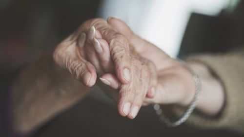 Holding hand of old woman