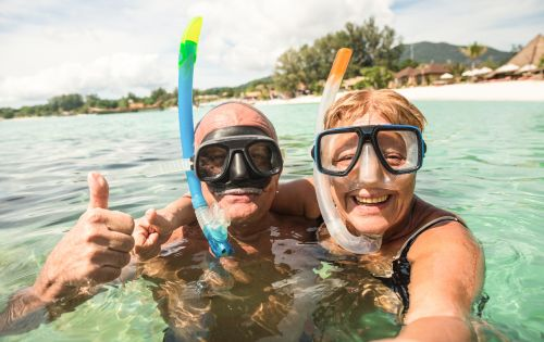Senior couple taking a selfie while snorkeling on a tropical sea excursion