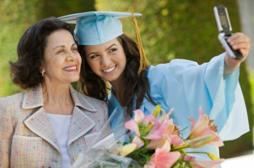 College Graduate and Grandmother Taking Picture with Cell Phone