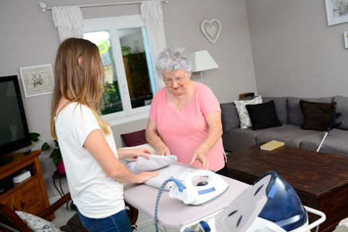 Woman Helping Grandmother with Ironing